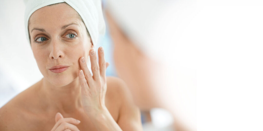 Frau mittleren Alters, die Gesichtscreme aufträgt