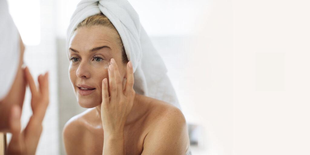 Frau mittlern Alters, die in den Spiegel schaut und sich Augencreme aufträgt
