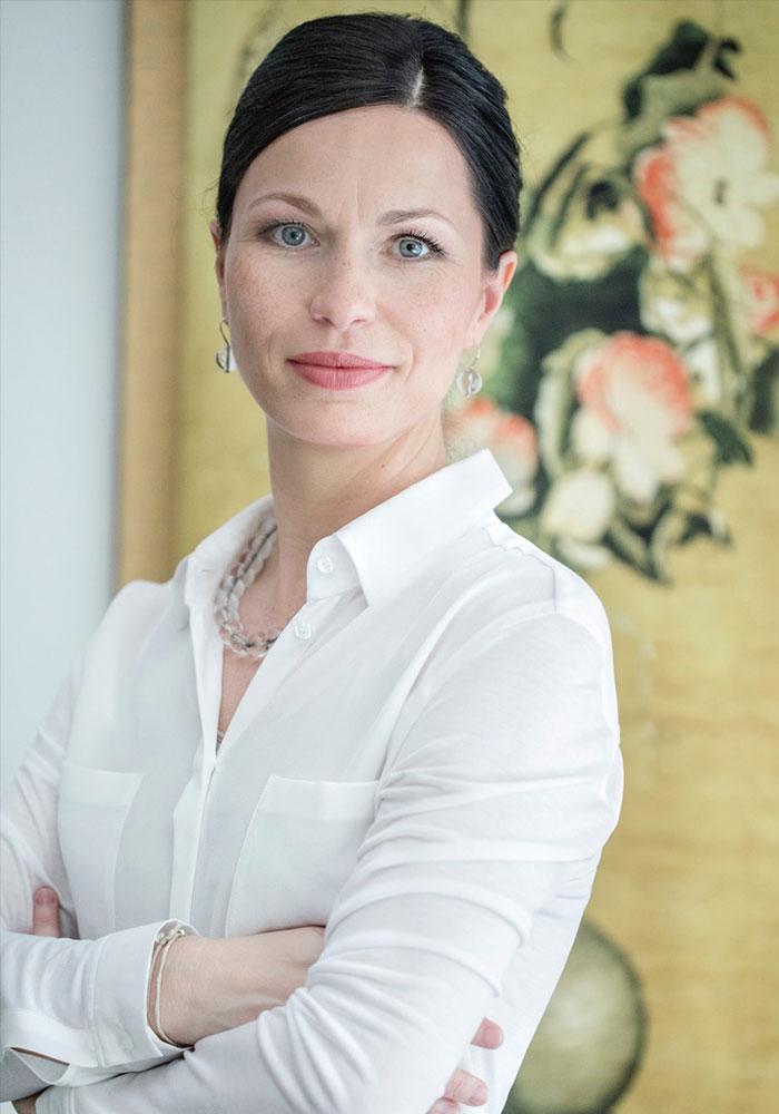 Sabine Schmitz mit chinesischem Bild im Hintergrund